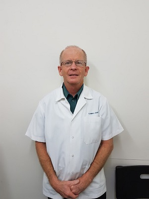 Bryan dowse dentist standing in front of a white wall